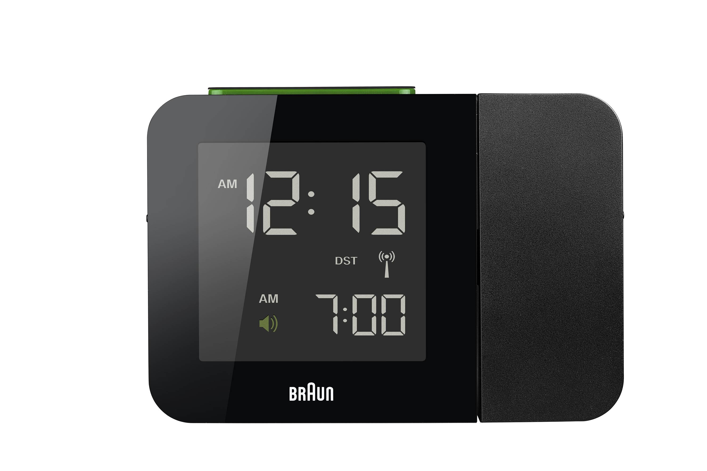Zwarte projectiewekker van Braun met groene knop. tijd en alarm zijn afgebeeld.