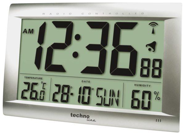 grote zilveren digitale klok met de tijd, temperatuur,datum en dag en luchtvochtigheid. in zwarte letters.
