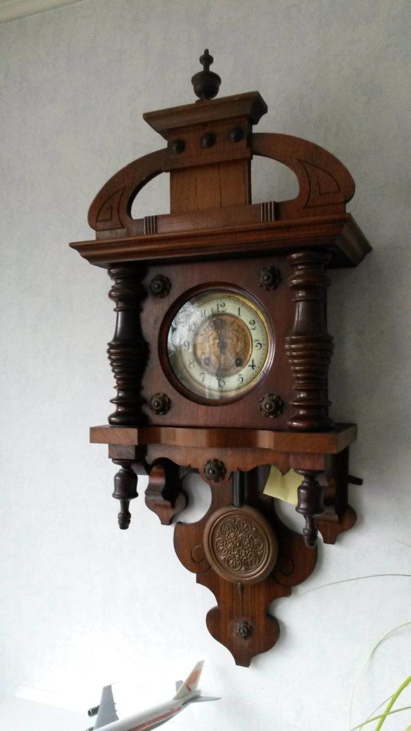 zijaanzicht weense regulateur van donker houtmet versieringen rondom,klokje achter glas en een versierde slinger.