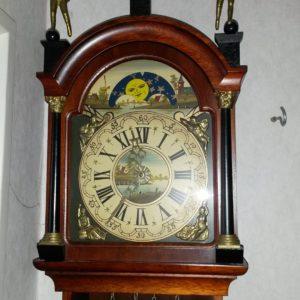 detail van authentieke Friesche klok donker hout met bronzen detailwerk, romeinse cijfers en beschildering