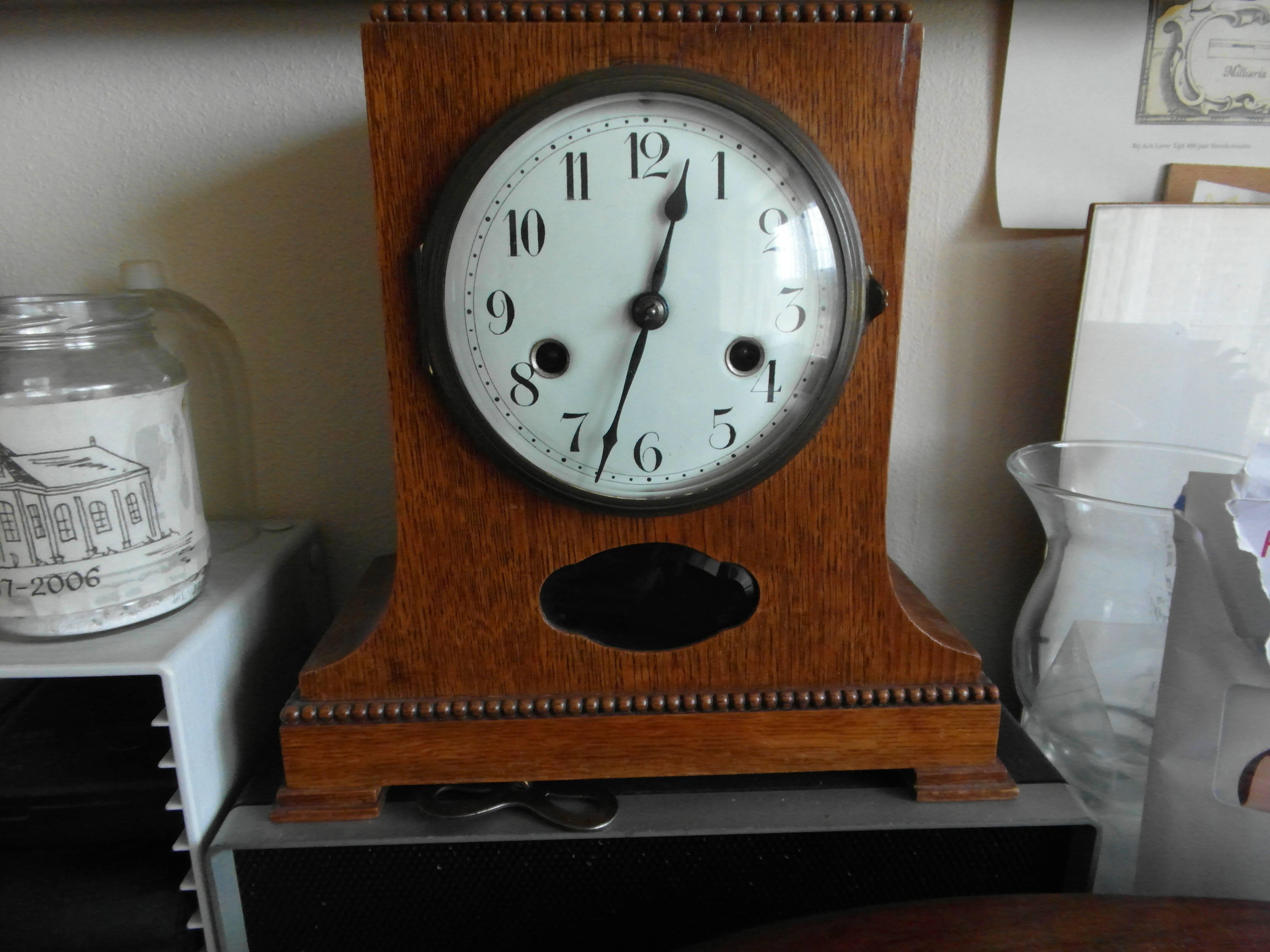 vooraanzicht van houten pendula klok met sierrand, witte wijzerplaat en zwarte cijfers.