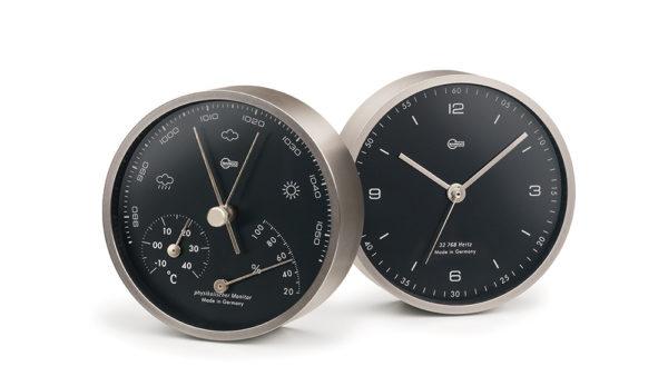 Vooraanzicht van stijlvolle kleine klok en hygrometer, barometer, thermometer combinatie. zwarte wijzerplaten en donker chromen lijst, witte rustige cijfes en wijzers.