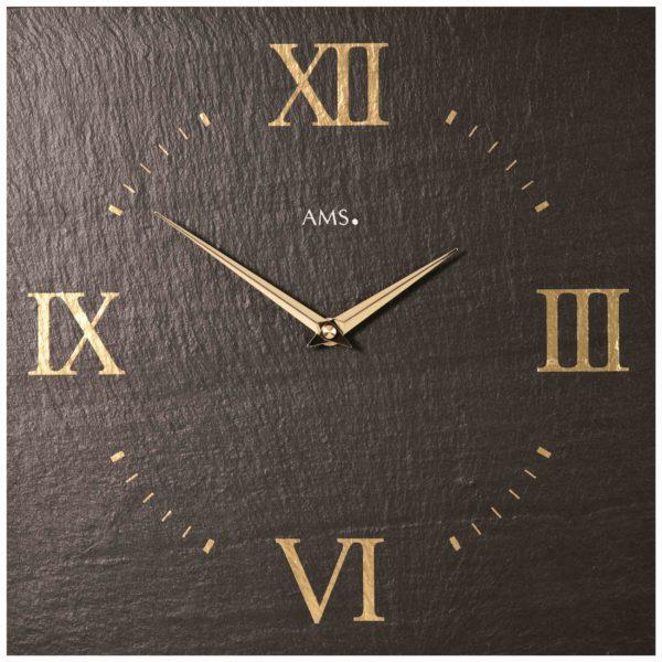 Donkergrijze leistenen vierkante klok met gouden details en romeinse cijferaanduiding.