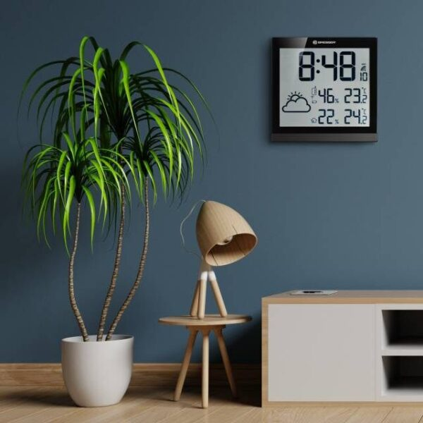 LCD Weer Wandklok TemeoTrend JC sfeerimpressie hangend op muur met lamp en plant ernaast.