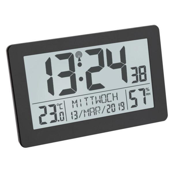 Vooraanzicht Digitale Klok Nederlands van TFA, geen logo afgebeeld, met zwarte lijst en letters/cijfers. De tijd, de temperatuur, de weekdag met datum en de luchtvochtigheid staan afgebeeld.