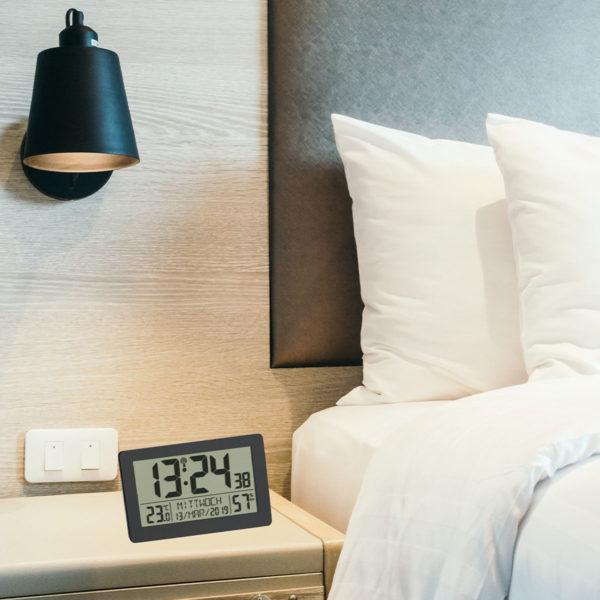 Sfeerfoto van de Digitale Klok Nederlands met een bed, nachtkastje en nachtlamp afgebeeld. p het nachtkastje staat de digitale klok met tijd, temperatuur, luchtvochtigheid en weekdag met datum.