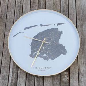 Vooraanzicht fryske klok met op de wijzerplaat kaart van Friesland met waddeneilanden in het zwart. witte achtergrond, messing lijst en wijzers.