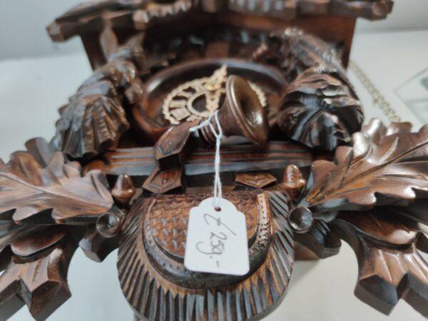 Detailfoto onderaanzicht notenhouten koekoeksklok met eikenblad
