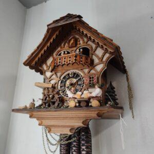 Een Beiers huisje of taverne bierdrinkers koekoeksklok met dansende stelletjes op het balkon, bierdrinkers op de vloer, denneboom, van hout met stalen gewichten van dennenaalden
