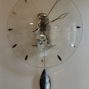 Vooraanzicht zilveren skeletklok met glazen wijzerplaat en zilveren details en slinger. je ziet de binnenkant van de klok, het uurwerk is ontbloot