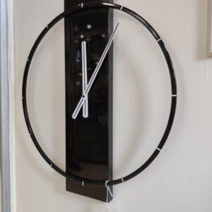 Nextime zwarte glanzende minimalistische klok met zilveren details en wijzers. de wijzerplaat is rechthoekig hout met een cirkel eromheen.