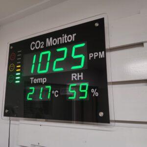 Rechthoekige zwart glazen co2 monitor met groene cijfers, witte tekst en indicatie emoji of emoticon voor luchtgezondheid en luchtkwaliteit met luchtvochtigheid en temperatuur