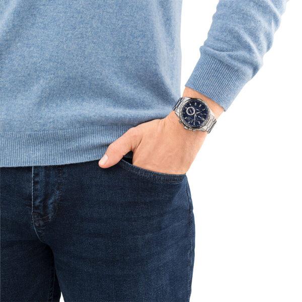 Mannenpols met Citizen Super Horloge AT8218-81L om met zilveren band en blauwe wijzerplaat.